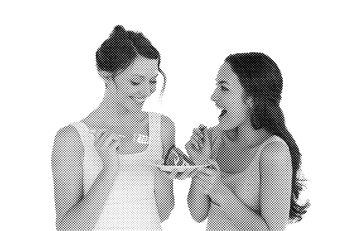 two women eating a piece of cake together.